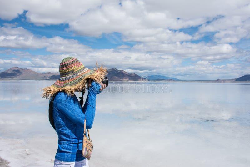 Turisten för den vuxna kvinnlign som bär en sugrörhatt, tar foto på Bonneville de salta lägenheterna royaltyfri foto