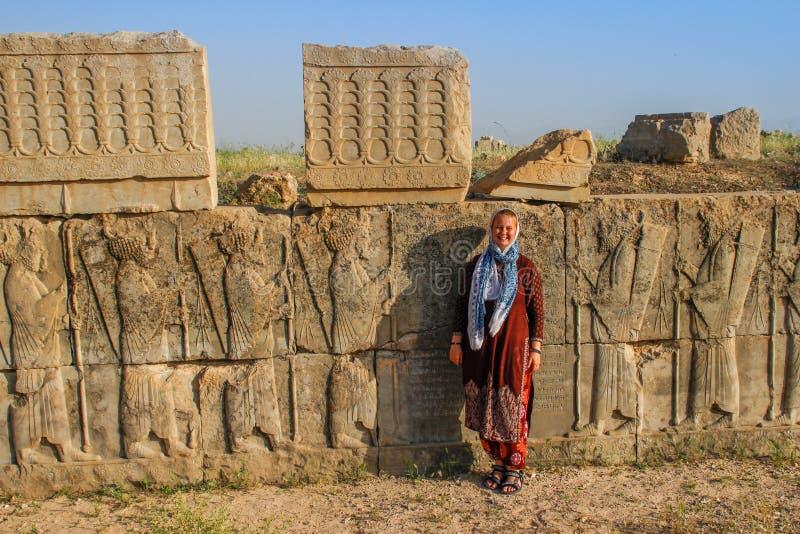 Turisten f?r den unga kvinnan med ett t?ckt huvud st?r p? bakgrunden av de ber?mda basrelieferna av daghuvudstaden av Persia Iran royaltyfria foton