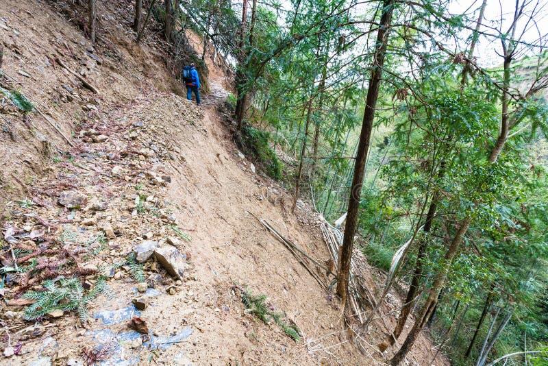 turisten går på banan till och med mudslide på berget arkivfoton