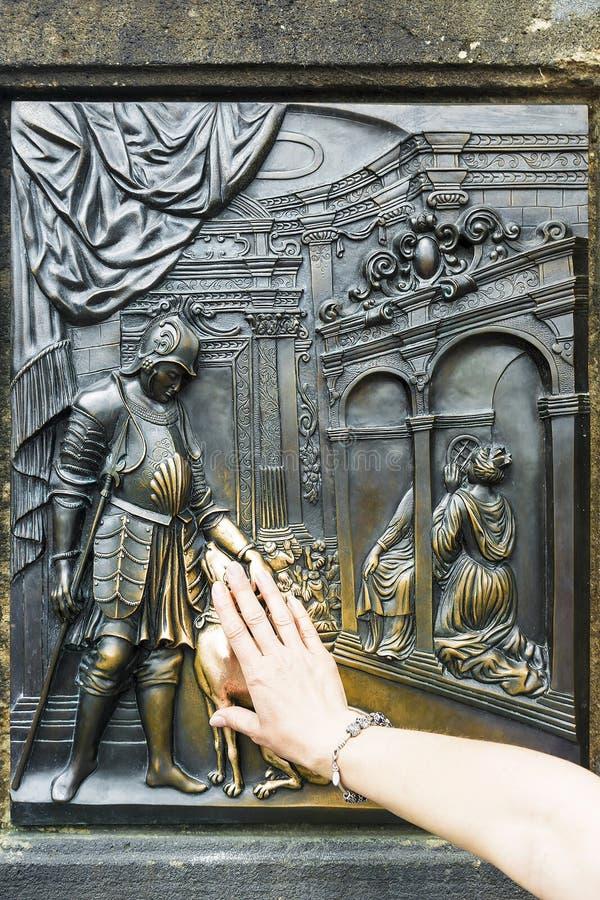 Turisten gnider brons minnes- platta av Saint John av Nepomuk arkivfoto