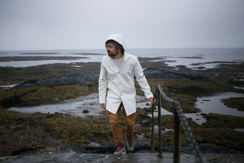Turisten i den vita regnrocken går på den Island kusten royaltyfria bilder