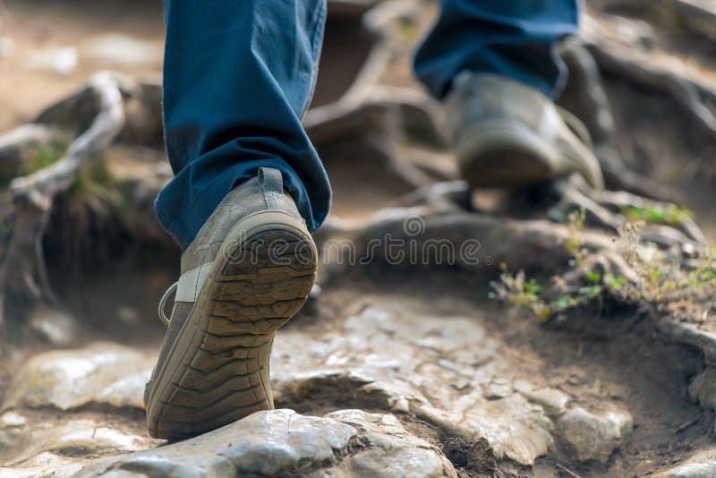 turisten klättrar upp berget, hans bennärbild arkivfoton