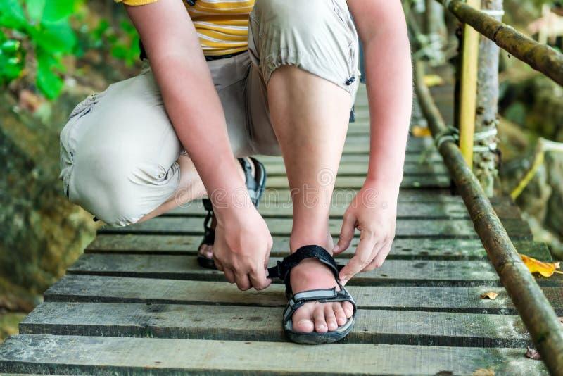 Turisten korrigerar omfamningen på sandalerna royaltyfri bild