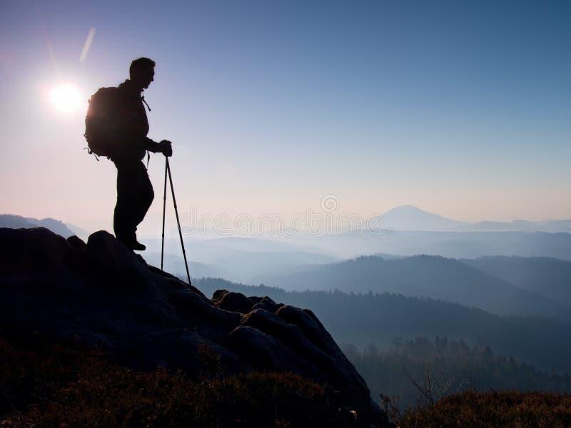 Turisten med den sportiga ryggsäcken och poler i händer står på stenig siktspunkt och att hålla ögonen på in i dimmig dalbröl för royaltyfri fotografi