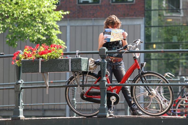 Turisten med kartlägger och cyklar. Amsterdam Nederländerna. arkivfoton