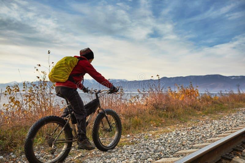 Turisten rider en cykel med breda hjul längs kusten av Lake Baikal royaltyfria bilder