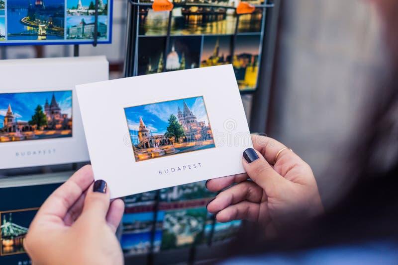 Turisten rymmer en vykort med en bild av ett populärt ställe i Budapest royaltyfri foto