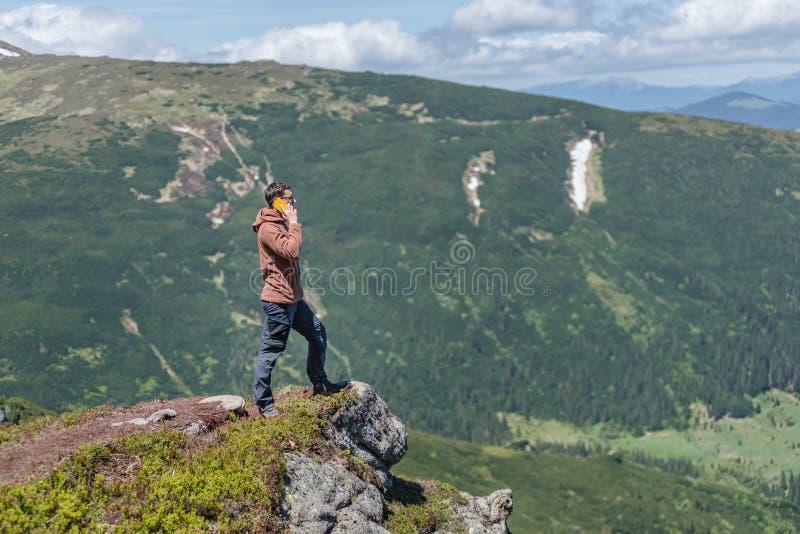 Turisten står på de mountan klipporna som talar på smartphonen fotografering för bildbyråer