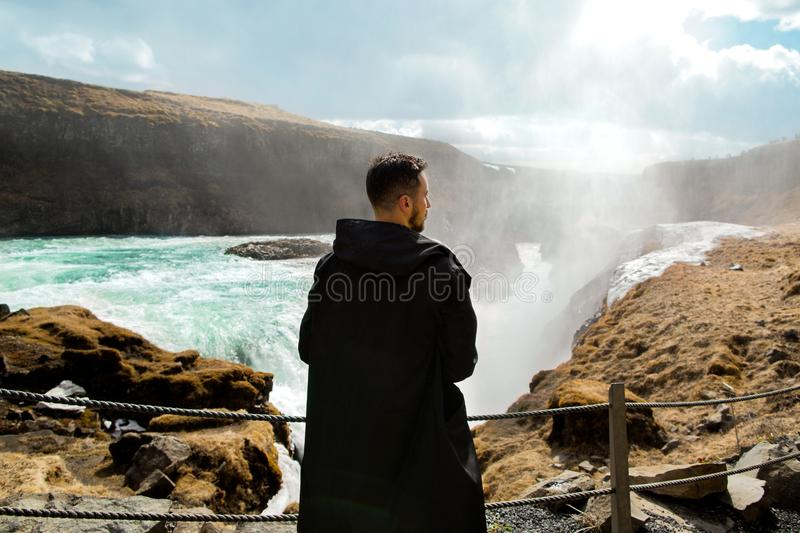 Turisten står på en klippa nära en vattenfall, begreppet av arkivbild
