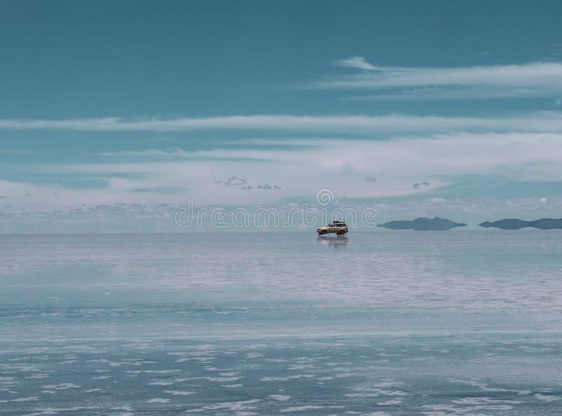 Turisten turnerar för saltar lägenheter i Salar de Uyuni royaltyfria foton