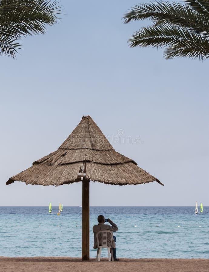 Turisten vilar på den centrala stranden av Eilat arkivfoto