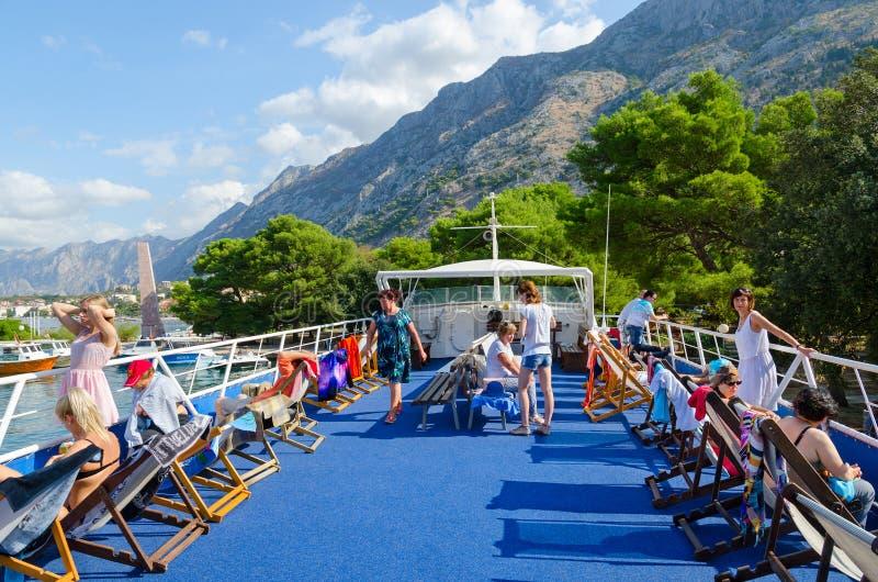 Turister är på övredäck av nöjeskeppet, innan de ställer av in på, turnerar av fjärden av Kotor, Montenegro arkivbild