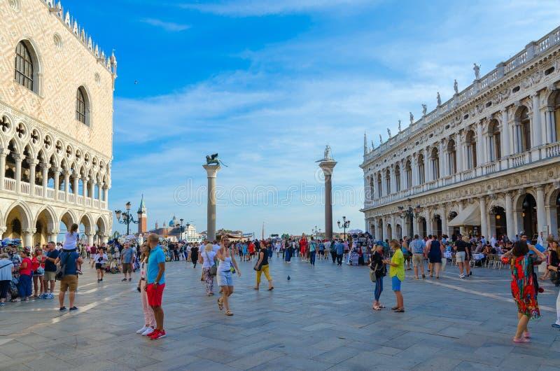 Turister är på den berömda piazza San Marco nära slott för doge` s och Marciana Library, Venedig, Italien royaltyfri foto