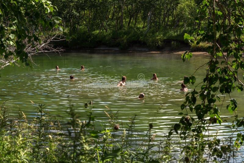 Turister badar i Khodutkinskiye Hot Springs på foten av vulkan Priemysh royaltyfri fotografi