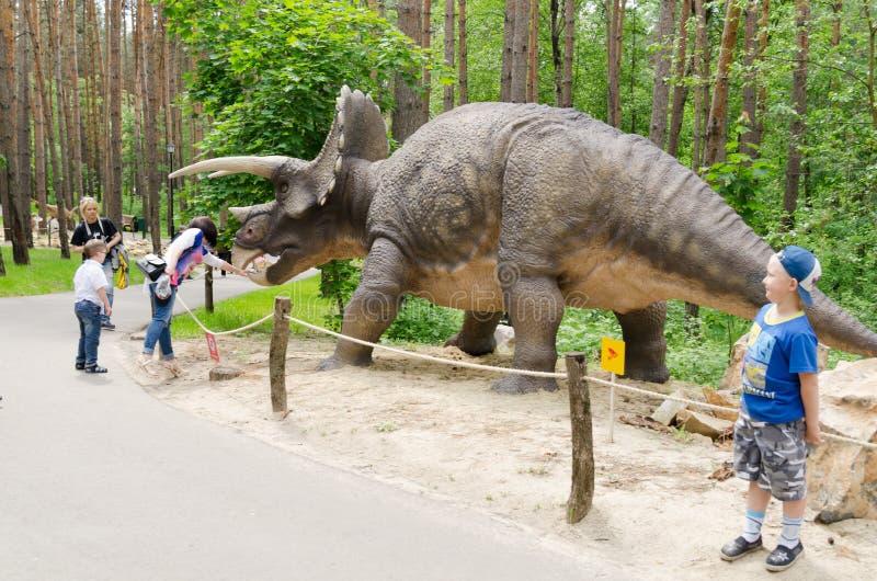 Turister betraktar dinosauriemodellen Triceratops arkivbild