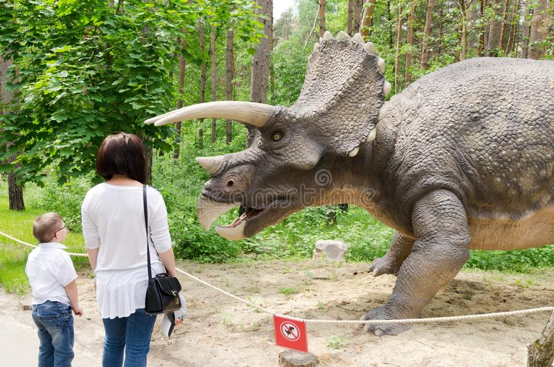 Turister betraktar dinosauriemodellen Triceratops royaltyfri fotografi