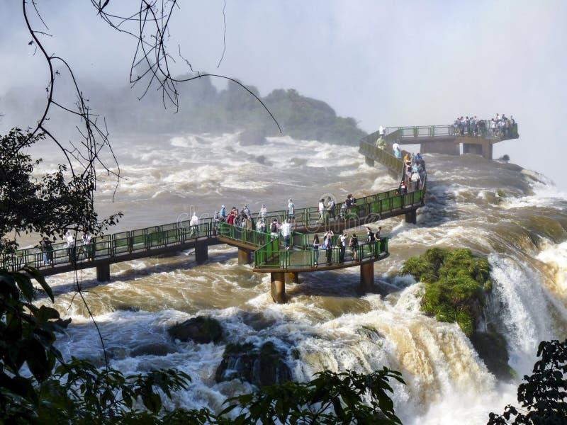 Turister beundrar Iguacu (Iguazu) nedgångar på en gräns av Brasilien och royaltyfria bilder