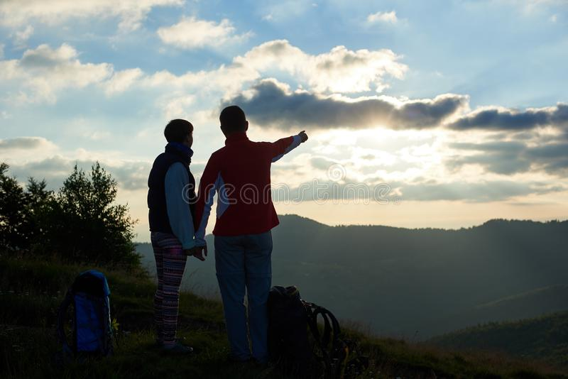 Turister för bakre sikt två står överst av berget mot molnig himmel på solnedgången arkivbilder
