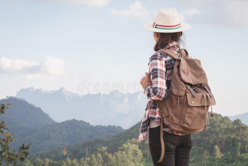 Turister för tonårs- flicka står och ser det härliga berglandskapet som överst strosar med en avslappnande ryggsäck av klippan royaltyfri fotografi