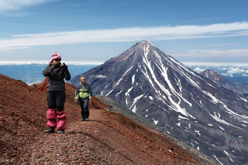 Turister för unga kvinnor som går ett berg som fotvandrar slingan på krater av den aktiva vulkan arkivfoto