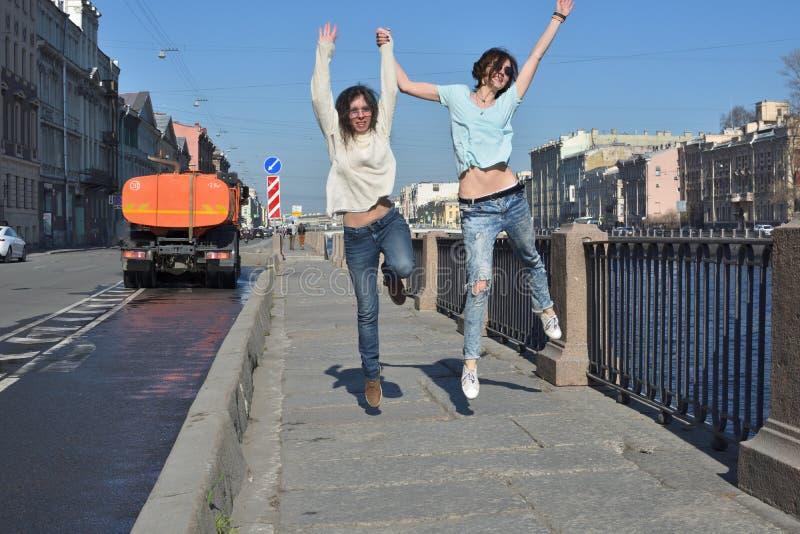 Turister f?r unga damer i St Petersburg Ryssland har gyckel tillsammans p? en solig dag, kl?r av och hoppar av gl?dje royaltyfria bilder