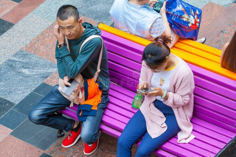 Turister från Asien sitter på en bänk med telefonledaren arkivfoto