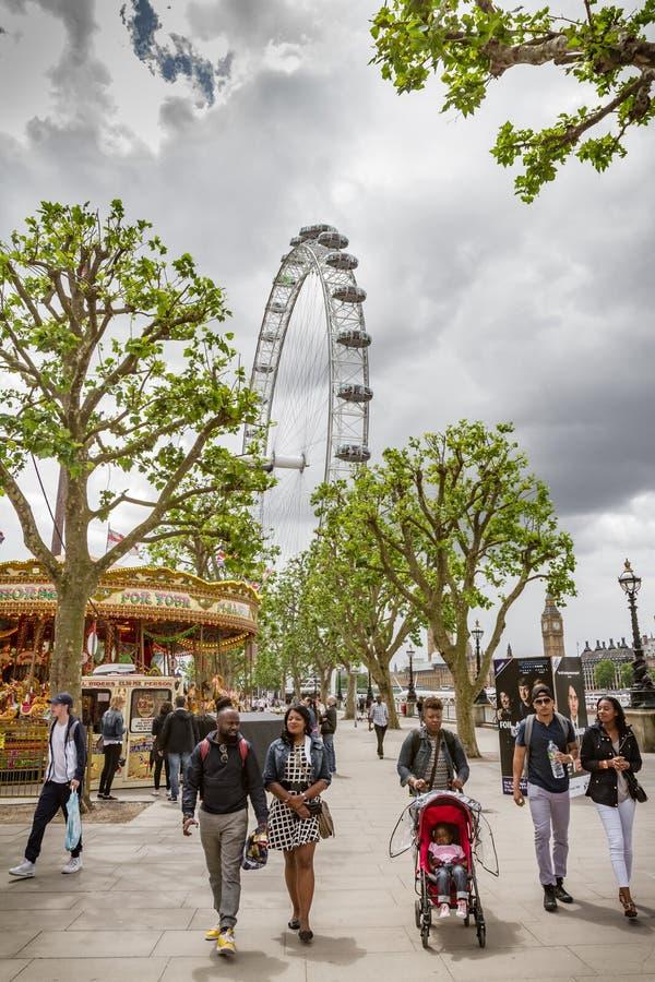 Turister går förbi det London ögat på Southbanken arkivbilder