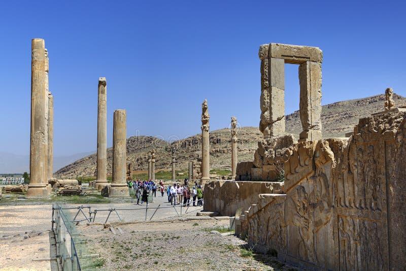 Turister går förbi pelare fördärvar på av forntida Persepolis, Iran arkivbild