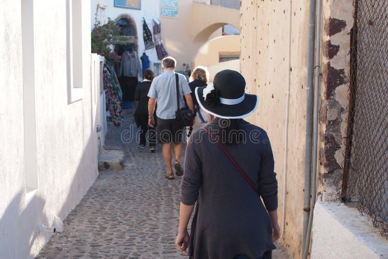 Turister går ner den smala stadsgångbanan royaltyfri foto