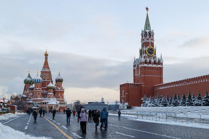 Turister går på den röda fyrkanten på en kall vinterafton arkivbild