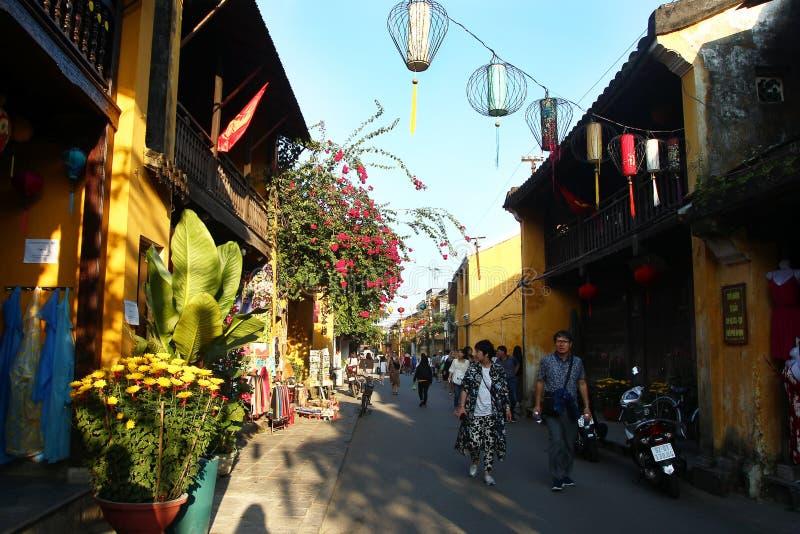 Turister går på en gata av den gamla historiska mitten Hoi An med gula byggnader, shoppar och färgrika kinesiska lyktor royaltyfria bilder