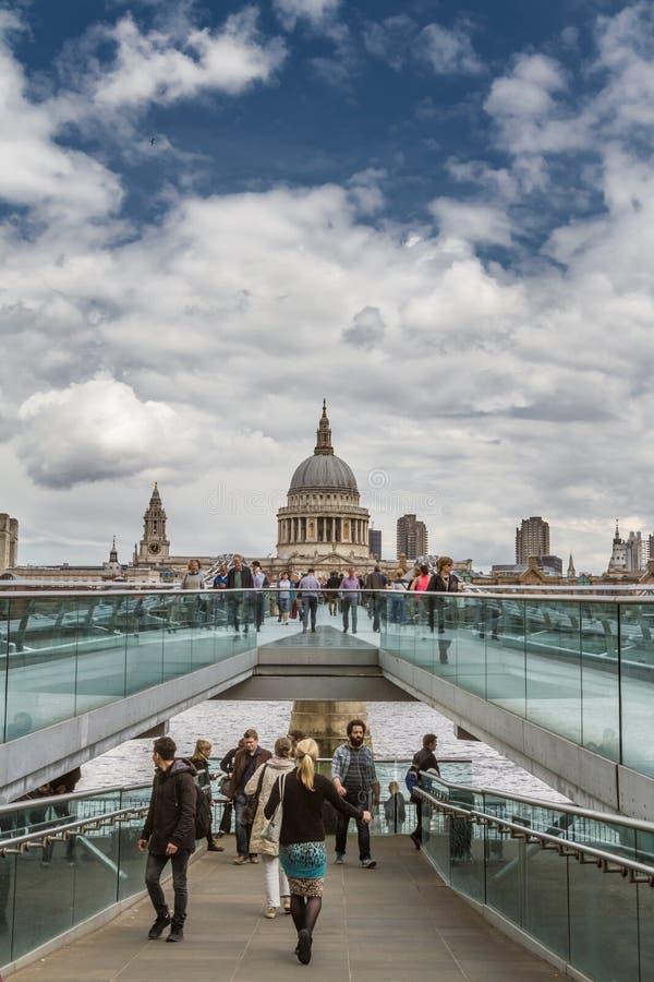 Turister går på milleniumbron med St Pauls i bakgrund royaltyfri fotografi