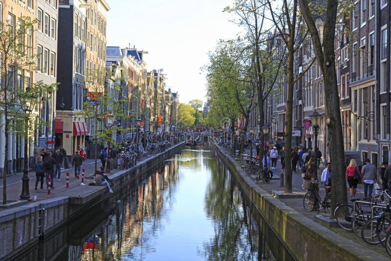 Turister går på rött ljusområdet i Amsterdam, Nederländerna arkivfoto