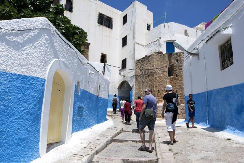 Turister går till och med de härliga gatorna av Kasbah des Oudaias i staden av Rabat, Marocko royaltyfria foton