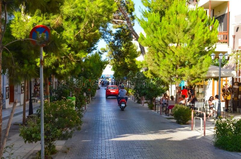 Turister går till och med de pittoreska gatorna av Agios Nicolas arkivbild