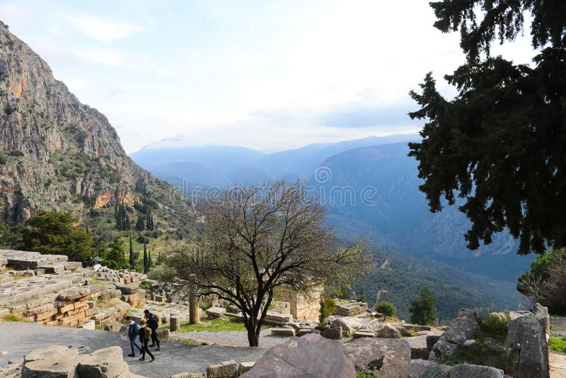 Turister går till och med fördärvar av forntida Delphi med dalen och berg som ut sträcker i bakgrunden arkivbild