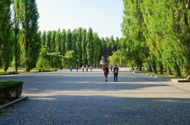 Turister går till skulptural sammansättning som den sorgsna modern i Treptow parkerar, Berlin, Tyskland royaltyfri foto