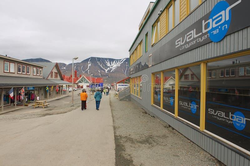 Turister går vid gatan av Longyearbyen, Norge arkivbild