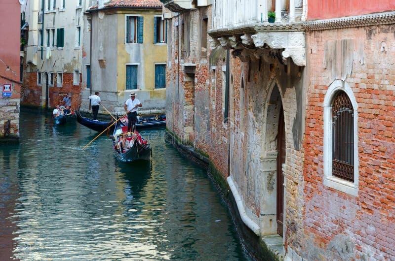 Turister gör romantiker går på gondoler längs kanaler av Venedig, Italien royaltyfria foton