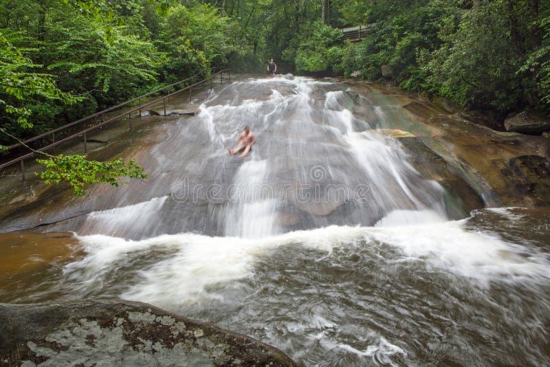Turister glider ner en North Carolina vattenfall arkivbild