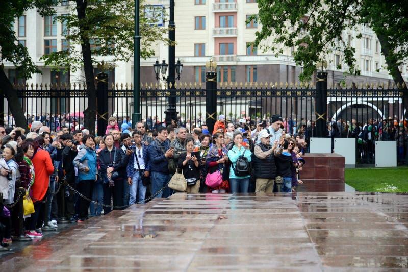 Turister håller ögonen på ändringen av vakten av heder på graven av en okänd soldat i Alexander Garden arkivfoton
