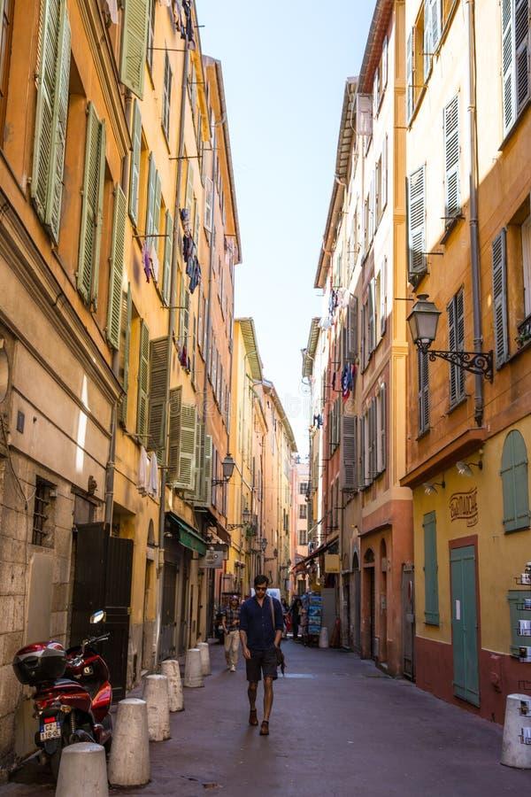 Turister i gammal smal gata i Nice, franska riviera `-Azurer för skjul D solig ljus dag royaltyfria bilder
