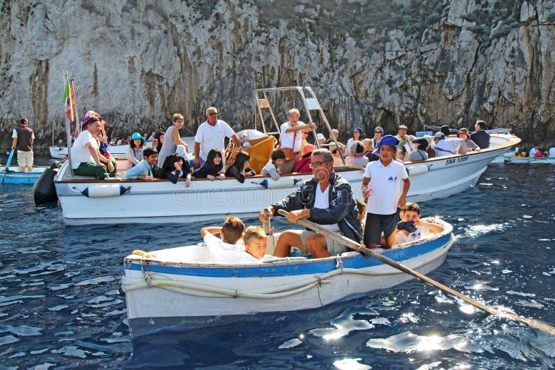 Turister i små fartyg som väntar för att skriva in den blåa grottan på Capr arkivbilder