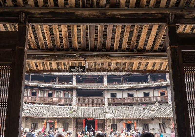 Turister inre Tulou på den Huaan Unesco-världsarvet royaltyfri fotografi