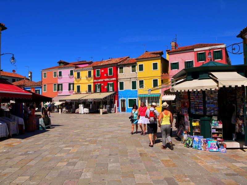 Turister irrar i den huvudsakliga fyrkanten på ön av Burano Italien arkivfoto