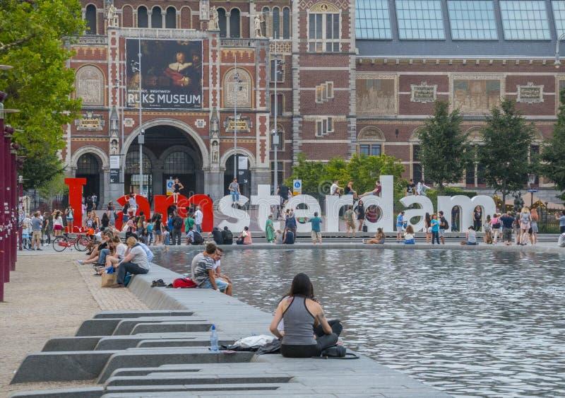 Turister kopplar av på det nationella museet Amsterdam - AMSTERDAM - NEDERLÄNDERNA - JULI 20, 2017 arkivfoto