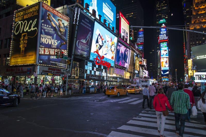 Turister kvadrerar tidvis på natten, det berömda läget i New York City som är fullt av folk och bilar och dess tecken för neonlju arkivbild