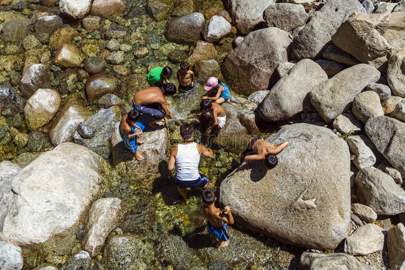 Turister kyler deras ben i sjön av den lägre Yosemite waten royaltyfri bild
