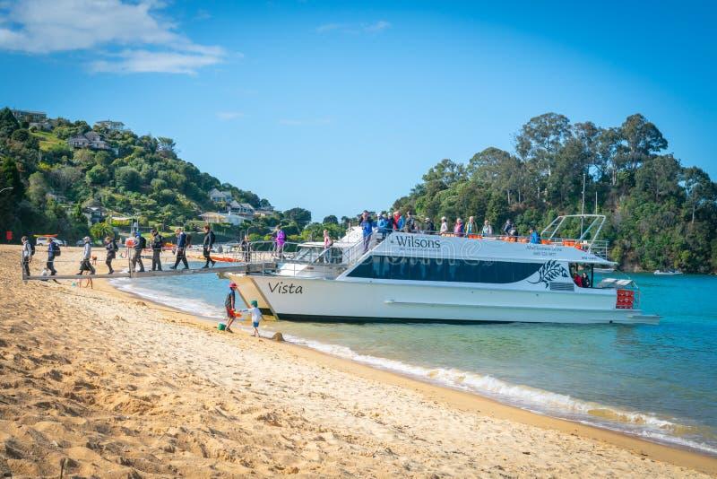 Turister landsätter på den Kaiterteri stranden Tasman Nya Zeeland arkivbild