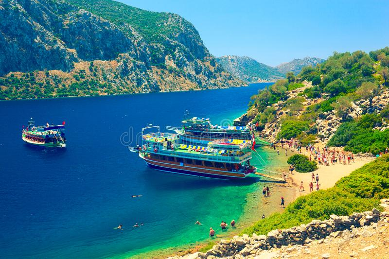 Turister matar getterna på den sandiga stranden av den Kamelya ön medan fartygturen till Aegean öar arkivbild